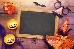 Pumpkins, spiders, bats and blackboard on wooden old table Stock Photos