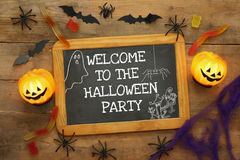 Pumpkins, spiders, bats and blackboard on wooden table Stock Photos