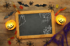 Pumpkins, spiders, bats and blackboard on wooden table Stock Image