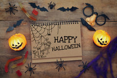 Pumpkins, spiders, bats and notebook on wooden background Royalty Free Stock Photos
