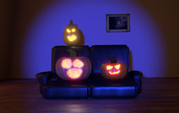 Pumpkins watching tv. Lighten horrified pumpkins watching tv at night at the living rom royalty free stock photography