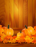 Pumpkins on wooden background with leaves Royalty Free Stock Images