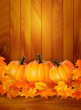 Pumpkins on wooden background with leaves Stock Photo