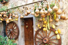 Pumpkins and wooden wheels. Pictoresque corner in the village of Castelnuovo Berardenga, Siena, Tuscany, Italy Royalty Free Stock Images