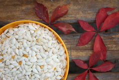 Pumpkinseeds. In the bowl and autumn leafs Stock Photo