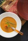 Pumpkinsoup su un piatto bianco con il fiore commestibile fotografie stock libere da diritti