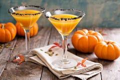 Pumpkintini pumpkin martini coctail. With black salt rim for fall and halloween parties Stock Photos