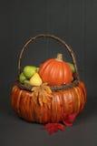 Pumpor och äpplen i korg-, nedgång- eller tacksägelsetema Royaltyfria Foton