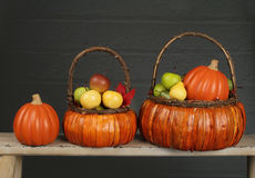 Pumpor och äpplen i korg-, nedgång- eller tacksägelsetema Fotografering för Bildbyråer