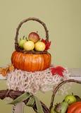 Pumpor och äpplen i korgar på den Wood bänken Fotografering för Bildbyråer