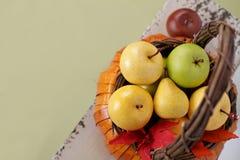 Pumpor och äpplen i korgar på den Wood bänken Arkivfoton