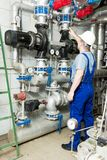 Pumps and pipes. Specialist looks at the pumps and pipes Stock Photography