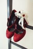 Pumpt rotes Gämsenleder der Damen Schuhe auf einer Metallfeuerleiter am Balkon Brautzubehör in einem Hochzeitstag Stockbilder