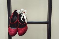 Pumpt rotes Gämsenleder der Damen Schuhe auf einer Metallfeuerleiter am Balkon Brautzubehör in einem Hochzeitstag Lizenzfreie Stockbilder