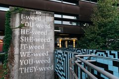 Pun with the word weed on concrete wall in Vienna. Vienna,  Austria - August 17, 2017: Sentences on concrete wall in museums quartier in Vienna with a pun with Royalty Free Stock Image