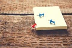 Punaise et papier sur la table en bois image stock