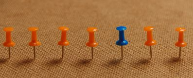 Punaise stationnaire et bleue dans la rangée avec l'orange, concept pour la différence, individualité, direction Copiez l'espace  Images stock