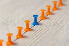 Punaise stationnaire et bleue dans la rangée avec l'orange, concept pour la différence, individualité, direction renaissance Copi Image stock