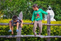 Punakha,不丹- 2016年9月10日:享受在庭院篱芭的两个逗人喜爱的小男孩阳光 免版税库存图片