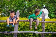 Punakha,不丹- 2016年9月10日:享受在庭院篱芭的两个逗人喜爱的小男孩阳光 库存照片