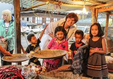 Free Punakha, Bhutan - September 10, 2016: Happy Caucasian Woman Posing With Bhutanese Kids In Bazaar With Yellow Light In Punakha. Royalty Free Stock Images - 102686009