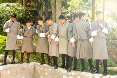 Punakha Bhutan - September 10, 2016: Bhutanesiska skolpojkar i deras skolalikformig på skolan arbeta i trädgården Royaltyfri Bild