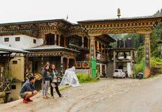 Punakha Bhutan - September 12, 2016: Bhutanesiskt folk som står på vägen nära traditionella byggnader på en regnig dag Arkivfoto