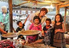 Punakha, Bhutan - September 10, 2016: Het gelukkige Kaukasische vrouw stellen met jonge geitjes Uit Bhutan in bazaar met geel lic royalty-vrije stock afbeeldingen