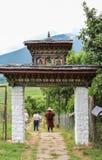 Punakha, Bhutan - September 11, 2016: Mensen die door poort aan Chimi Lhakhang (Klooster van Vruchtbaarheid) overgaan in Punakha, royalty-vrije stock afbeeldingen
