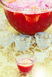 Punch. Cup of delicious punch with slices of oranges. Large punch bowl and empty cups in background. Shallow DOF with focus on filled cup stock image