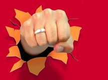 Punch. Composite image of fist punching a red paper wall, producing a hole Stock Image