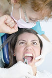 Punch the dentist. A young girl is scared at a tooth extraction Stock Photography