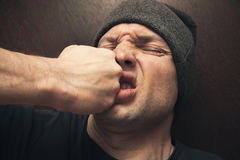 Punch in the face, street fight. Punch in the face of young angry Caucasian man royalty free stock photo