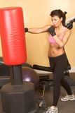 Punch girl kickboxing workshop. Attractive young woman training kickboxing using red punching bag to study self protection Royalty Free Stock Photo