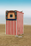 Punch & Judy. A red and white striped wooden punch and Judy booth on a beach located in Weymouth, Dorset UK. A seagull perches on top, with two seagulls pecking stock photography