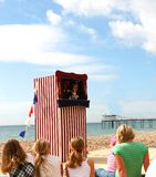 Punch and Judy by the seaside. Children watch an old fashioned Punch and Judy Show by the sea royalty free stock photo