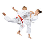 Punch in the jump and kick leg are beating the sportsmens in karategi Stock Photography