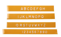 Punch letter alphabet on orange labeling tape Stock Photography