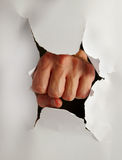 Punch out. Fist punching thru paper creating a torn hole Stock Photos