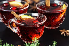 Punch. Red Christmas punch / drink with cinnamon, orange slices, anise and fresh cranberries over a dark background. Extreme shallow depth of field with royalty free stock images