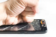 Punch in the screen of the phone. Broken smartphone. Punch on the screen Stock Photos