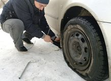 Punched and flat tire on the road. Replacing the wheel with a jack by the driver royalty free stock photo