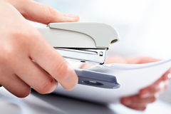Puncher. Close-up of female hand stapling the documents Royalty Free Stock Photography