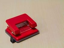 Puncher de agujero de papel rojo en fondo de madera Foto de archivo