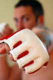Punching. A man punching towards the camera with fingerless mixed martial arts gloves Royalty Free Stock Images