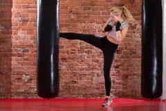 Λάκτισμα κοριτσιών punching στην τσάντα Στοκ φωτογραφίες με δικαίωμα ελεύθερης χρήσης