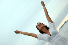 Punching the air. A beautiful, fit and healthy young woman throws her hands in the air in a fit of joy Stock Photos