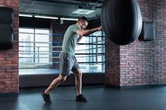 Punching ball abile di battitura del pugile mentre preparandosi nella palestra immagini stock