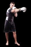 Punching boxer on black Royalty Free Stock Image
