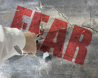 Punching, break concrete wall with word fear on it and small pie. Ces flying out Stock Photo